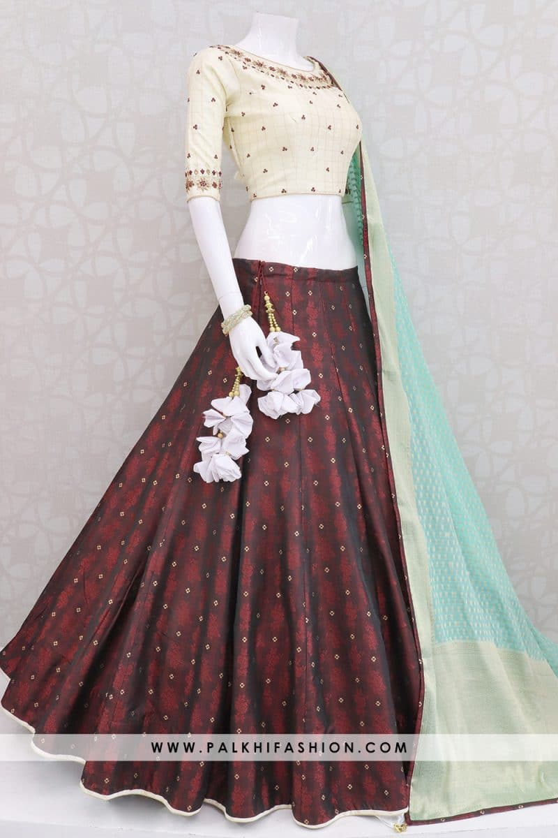 Palkhi fashion presents designer maroon lehenga with woven brocade designs.Beige handwork blouse with sea green georgette & silk weaving dupatta